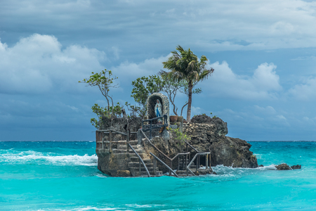 Willys Rock - an oddly shaped volcanic formation with a statue of the Blessed Virgin Mary at azure sea cloudy day in Bocaray, Philippine Islands.
