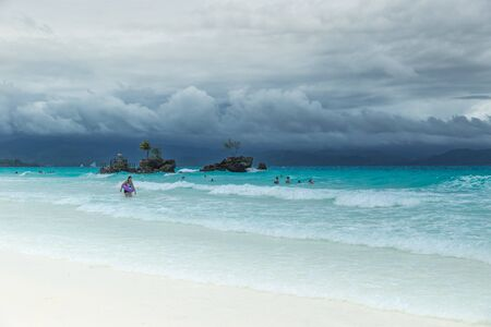 White Beach of Boracay and people swim at turquoise azure Sea on a cloudy day near Grotto Willys Rock upon which stands the Virgin Mary Statue. Boracay, Philippines. April 2018.