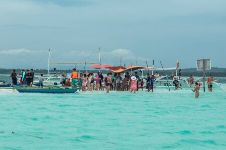 Chinese tourists and boats in the azure sea on the small Virgin island of Panglao, Bohol, Philippines. August 2018