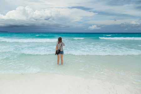 Happy traveller woman enjoys her tropical beach vacation