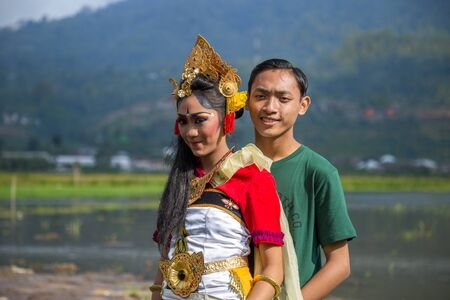 Balinese teens girl and boy in traditional costume on a balinese family ceremony in Bali, Indonesia. June 2018