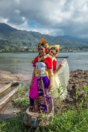 Portrait of Two Young Balinese traditional girls on the lake in the old boat in Bali, Indonesia. June 2018 新聞圖片