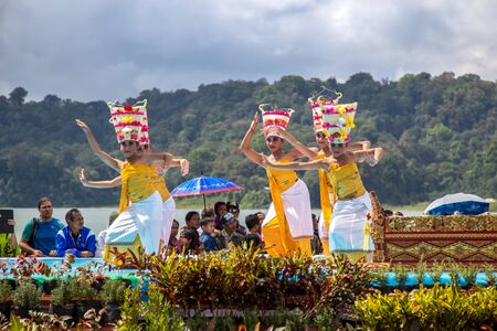 Young dancers in traditional costumes perform a welcome dance in Twin Lake Festival in Bali, Indonesia. June 2018
