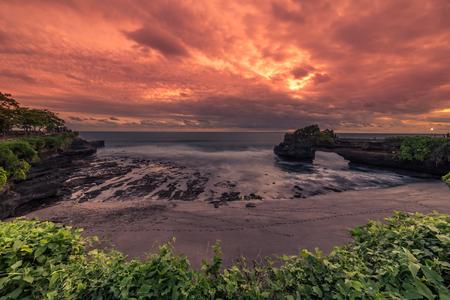 Amazing Sunset at rocky coast Pura Batu Bolong, Tanah Lot temple, Bali, Indonesia. 版權商用圖片