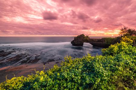 Colorful Sunset at rocky coast Pura Batu Bolong, Tanah Lot temple, Bali, Indonesia.