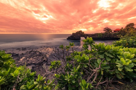 Incredible Sunset at rocky coast Pura Batu Bolong, Tanah Lot temple, Bali, Indonesia.