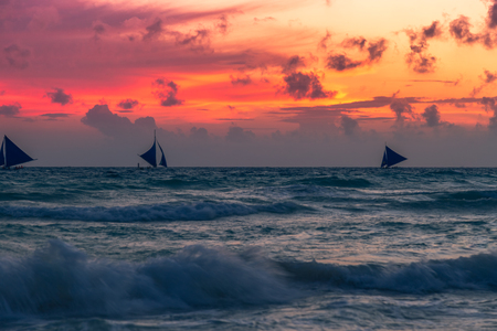 A sail boat yacht on the horizon at sunset silhouette against the setting sun orange sky behind clouds