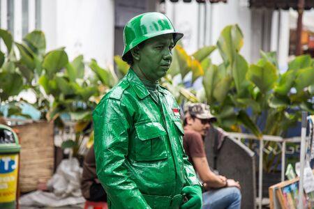 Street artist transformed into a green statue of a soldier. Jakarta, Jawa, Indonesia - Juli 2018