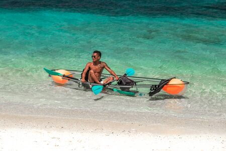 Glass kayak with a local man swimming turquoise sea in Bora Bora, Tahiti - January 2018 新聞圖片