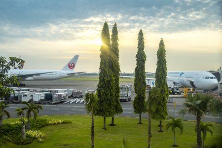 Aircraft at Ngurah Rai Airport in Bali airport runway at sunset time. Bali, Indonesia. January 2018 新聞圖片