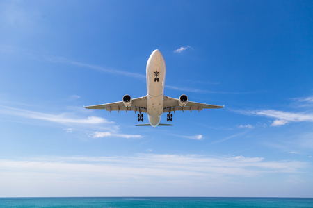 A passenger plane taking off in the cloudy sky. Aircraft flies over the sea and the tropical island. 版權商用圖片