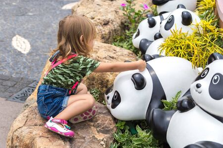 Adorable little girl playing with the statue toy panda in the park. Hong Kong, China. January 2018.