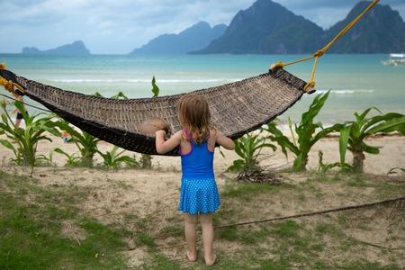 little girl standing backwards near to a hammock against a tropical beach 版權商用圖片