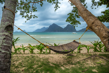 Traditional braided hammock in the shade with tropical island in the background 版權商用圖片