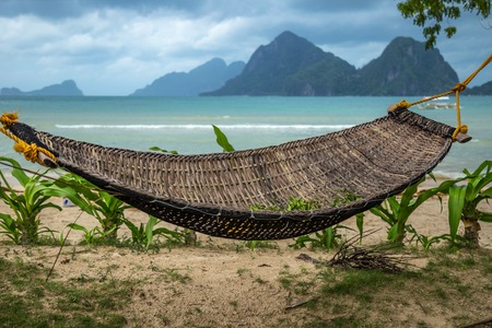 Traditional braided hammock in the shade with tropical island in the background 版權商用圖片 - 119756154