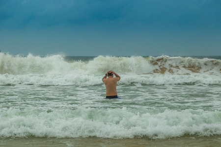 Man entering the sea at cloudy day 版權商用圖片