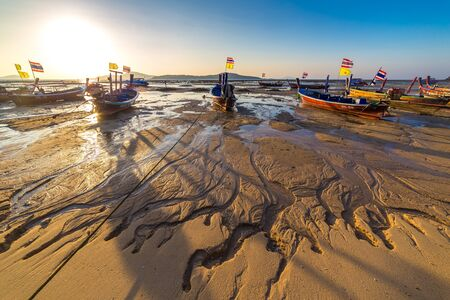 Fishing boats at low tide on the Chalong beach at sunrise time, Phuket, Thailand