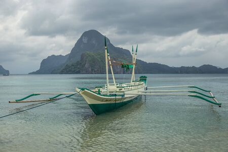 Fishing boat stranded and moored at the beach in a rainy morning in El Nido, Palawan, Philippines.