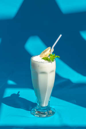 Banana milk smoothie with mint and drinking straw on abstract blue background.