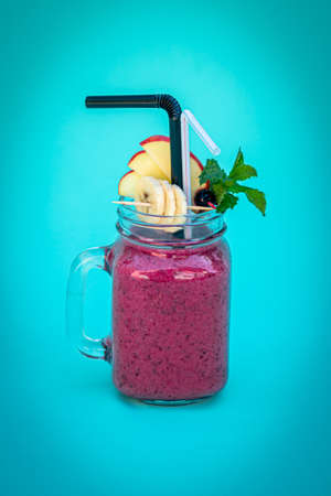 Pink smoothie with wild blueberry in mason jar with mint and straw on blue background. Archivio Fotografico