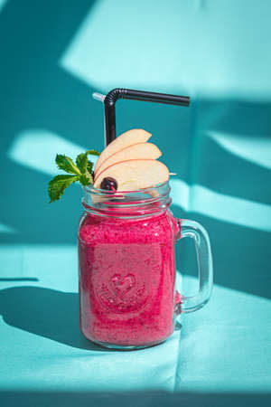 Pink smoothie with wild blueberry in mason jar with mint and straw on abstract blue background.