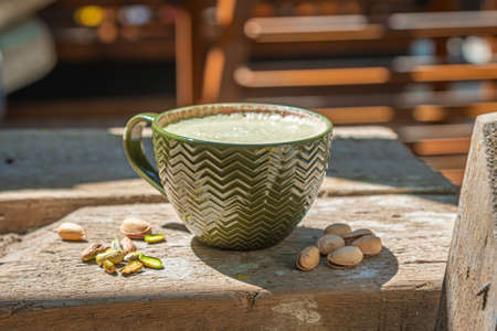 Delicious pistachio latte cup and nuts on old wooden table on abstract industrial background.