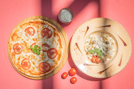 Italian fettuccine pasta and traditional pizza margherita with tomato on pink abstract background. Archivio Fotografico