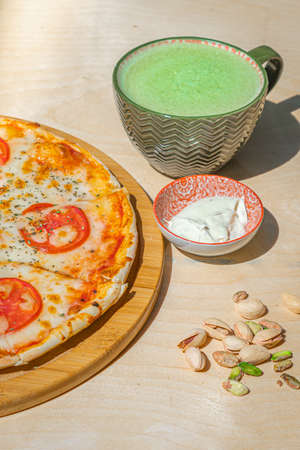 Japanese iced Matcha latte tea with pizza margherita and pistachios on wooden table.