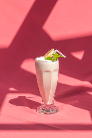 Banana milk smoothie with mint and drinking straw on abstract pink background.