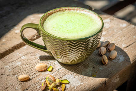 Pistachio coffee with tasty milk foam and pistachio nuts on old wooden table.