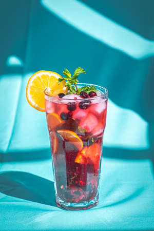 Ice refreshing summer drink with berry and lemon on abstract blue background. Archivio Fotografico