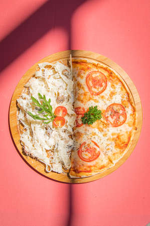Italian fettuccine pasta and traditional pizza margherita with tomato on wooden board on pink abstract background.