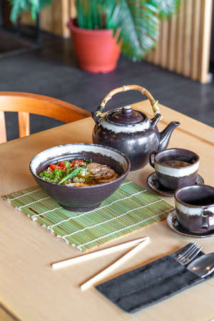 Japan Ramen noodles with broth in bowl serving size and Tea on table.