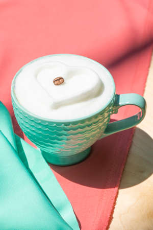Coffee drink with milk foam heart on pink and mint satin fabric.