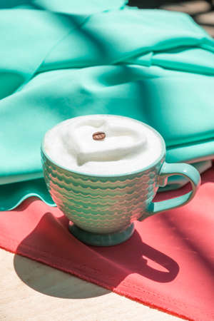 Latte with milk foam heart on pink and mint satin fabric. Archivio Fotografico