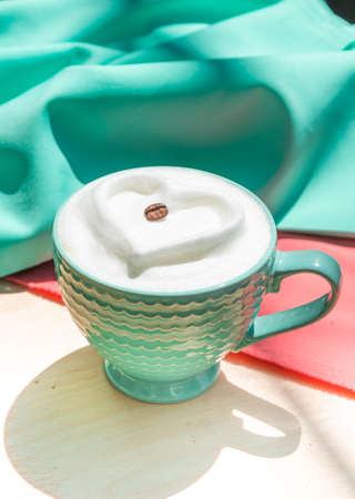 Cappuccino with milk foam heart on pink and mint satin fabric. Archivio Fotografico