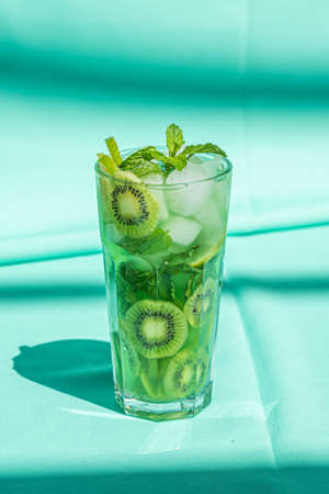Kiwi lime drink with mint and ice in glass close up on turquoise background. Archivio Fotografico