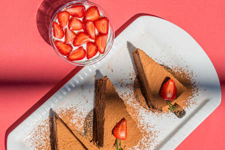 Chocolate cheesecakes with strawberries on pink abstract backgrount.