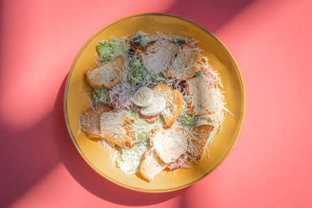 Cesar salad with roasted chicken meat on yellow plate on colorful pink background.