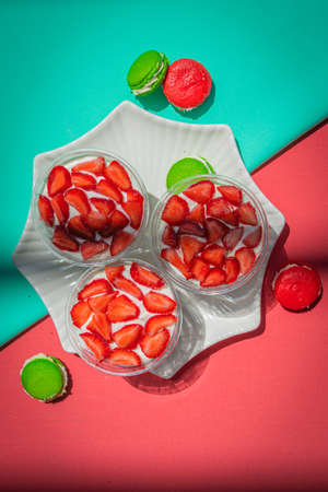 Strawberries in yogurt on a plate and french macarons on a bright abstract background.