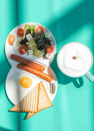 Fried eggs with sausages, tomatoes and toasts on white background on colorful green abstract background.