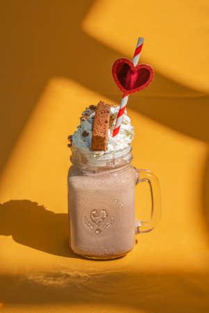 Chocolate milkshake in mason jar with a straw and heart on orange background with abstract shadows.
