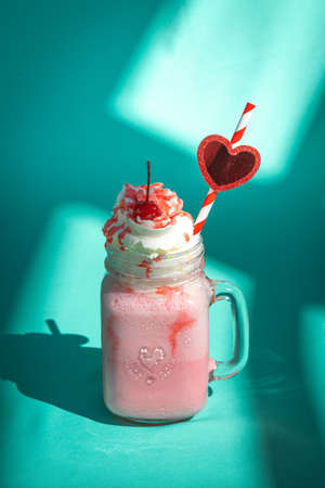 Milkshake with a cherry and whipped cream on mint turquoise background with abstract shadows.