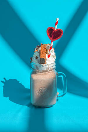Milkshake chocolate in jar with a straw and heart on blue background with abstract shadows.