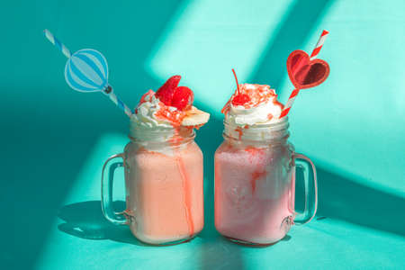 Pink milkshake raspberries smoothie in glass jar with whipped cream on colorful turquoise background with abstract shadows.
