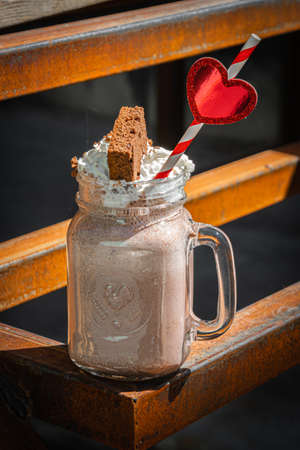 Milkshake chocolate with whipped cream and cake on rusty construction background.