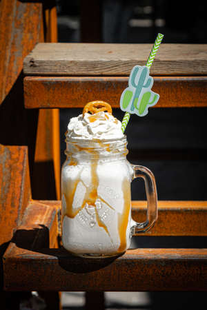 Banana milkshakes with caramel sauce and cookie on rusty construction background.