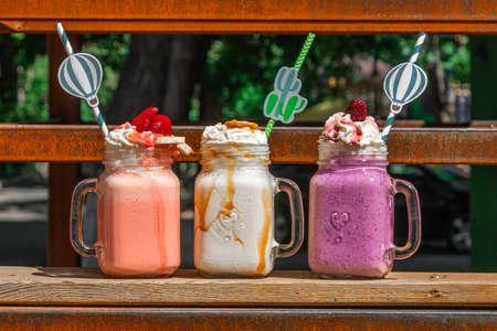 Three mason jars with milkshakes or smoothies. Summer healthy breakfast, lunch drinks - banana, strawberry milkshakes on old rusty background.