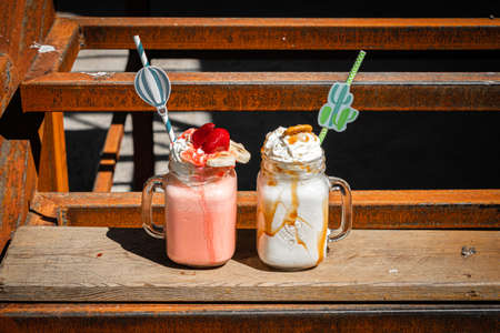 Mason jars of tasty milkshakes on old rusty rural background.