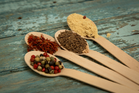 saffron, pepper, cumin and mustard in a wooden spoons. Stock Photo